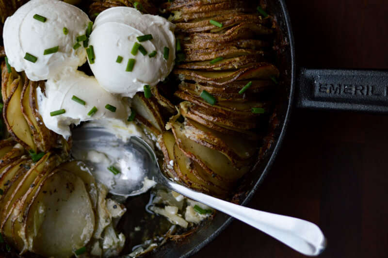 Hasselback Buttery Potato Ring in a cast iron skillet with a spoonful taken out of the pan.