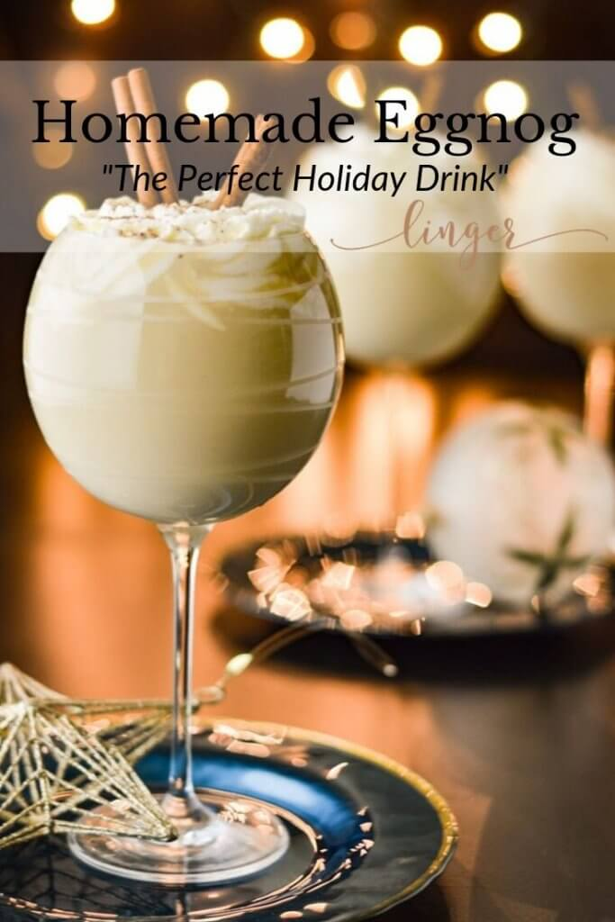 Three cocktail glasses of homemade eggnog. One is sitting on a blue saucer with a gold star ornament on it. Whipped cream top each glass with cinnamon sticks sticking out. Christmas lights are blurred in the background.