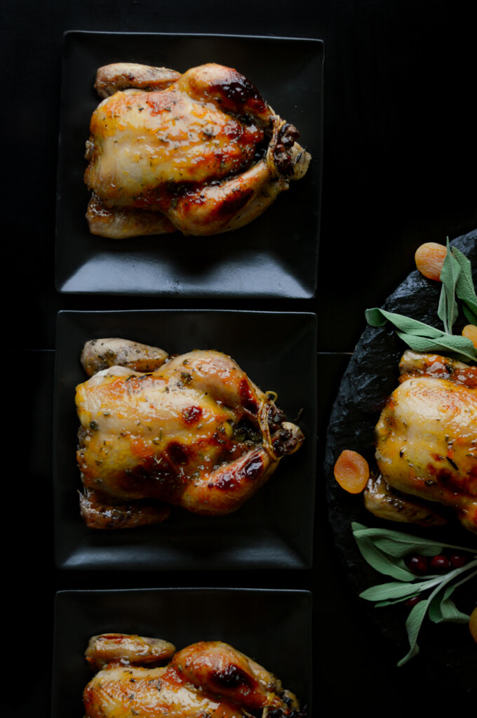 3 roasted stuffed Cornish Hens on 3 black plates next to a platter with another Cornish Hens.