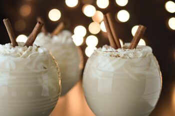 Eggnog with Bourbon in round wine glasses and cinnamon sticks