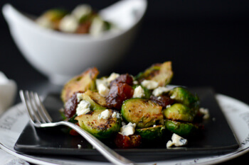 Brussel sprouts with blue cheese and craisins on a black plate with a fork