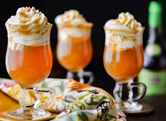 Three caramel apple hot toddy with whipped cream and caramel sauce dripping down the side.A bottle of apple brandy is blurred in the background.