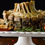 A crown roast of pork sitting on a white pedastal stand with rosemary sprigs as garnishment.