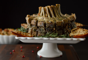 Stuffed Crown Roast of Pork on a white stand with rosemary and pomegranate seeds