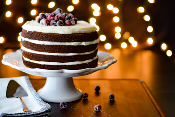 Gingerbread layer cake with eggnog frosting and fresh sugared cranberries on top