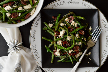 Green beans with feta, sundried tomatoes, olives on a black plate