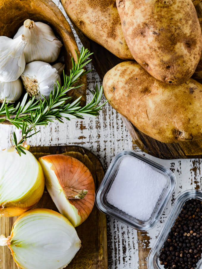 Russet potatoes sit on a wood board. Another wooden board holds 3 halved onions. A wooden bowl holds whole garlic and 2 sprigs of rosemary. Two small glass bowls hold salt and peppercorns.