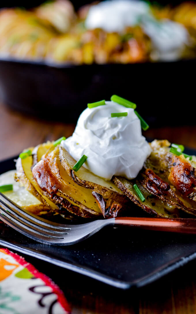 Hasselback potato ring dished up on a black pate with a garnishment of sour cream and chives. A cast iron skillet with potatoes sit in the background.