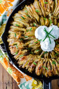 A hasselback potato ring in a cast iron skillet garnished with three dollops of sour cream and chopped chives. A colorful napkin sits beside the skillet.