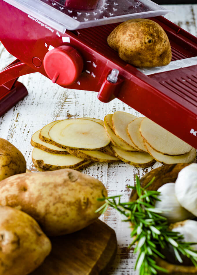 A red mandoline with sliced potatoes underneath. Whole potatoes, sprigs of rosemary and garlic sit i the forefront.