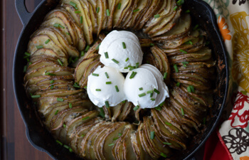 Slices of russett potatoes in a ring with sour cream and chives
