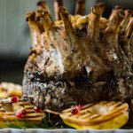 A cooked crown roast of pork sits on a white serving tray with grilled pears and fresh rosemary around the roast.