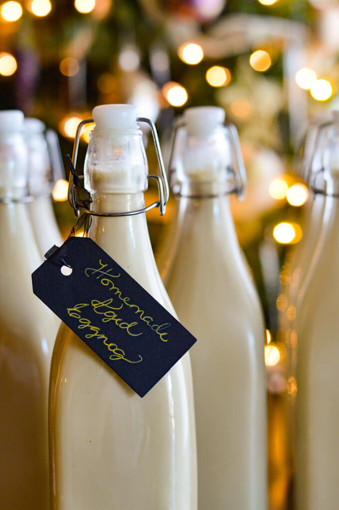 Bottles of Homemade Eggnog ready to give as Christmas gifts with a black tag on them.