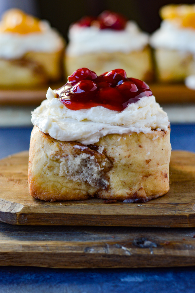 A front view of a cinnamon roll with cherry toppings on a wooden board with three cinnamon rolls in the background.