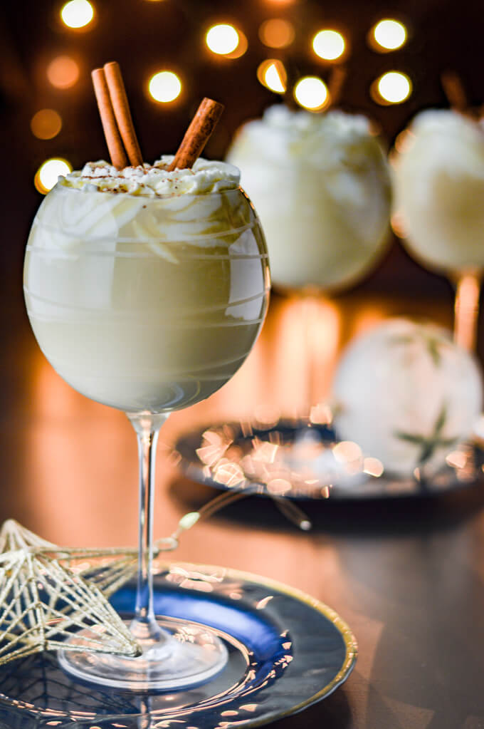 Three glasses of homemade eggnog topped with whipped cream and cinnamon sticks. A few glass ornaments sit next to them. Blurred Christmas lights are in the background.