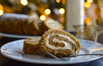 sliced pieced of pumpkin cake roll with eggnog bottle in the background