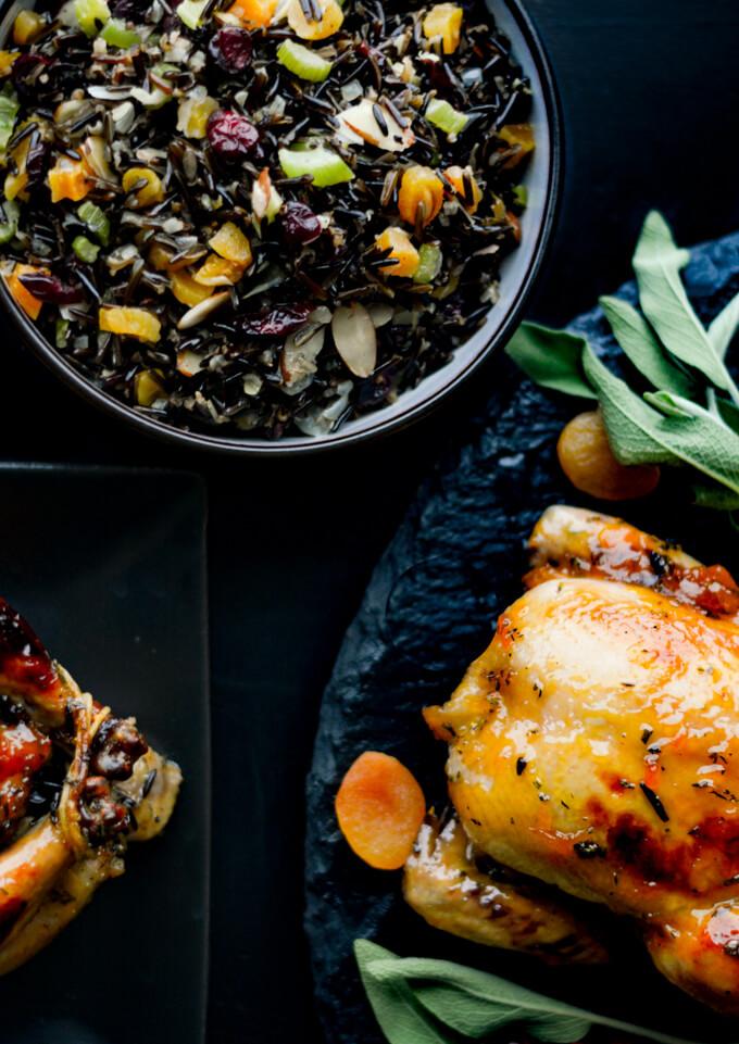 A bowl of wild rice stuffing with 2 cornish hens off to the side.