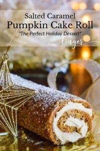 A baked salted caramel pumpkin cake roll with a gold star ornament next to it. There is ribbon, cellophane and Christmas lights in the background.