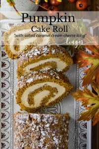 A pumpkin cake roll with three slices cut on a serving tray with fall leaves next to it.