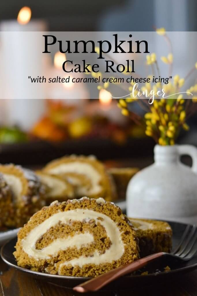 A slice of pumpkin cake roll sits on a black plate with a fork. There's a small white vase with yellow sprigs in it. A pumpkin roll with three slices sit in the background and candles lit in a container in the back is blurred out.