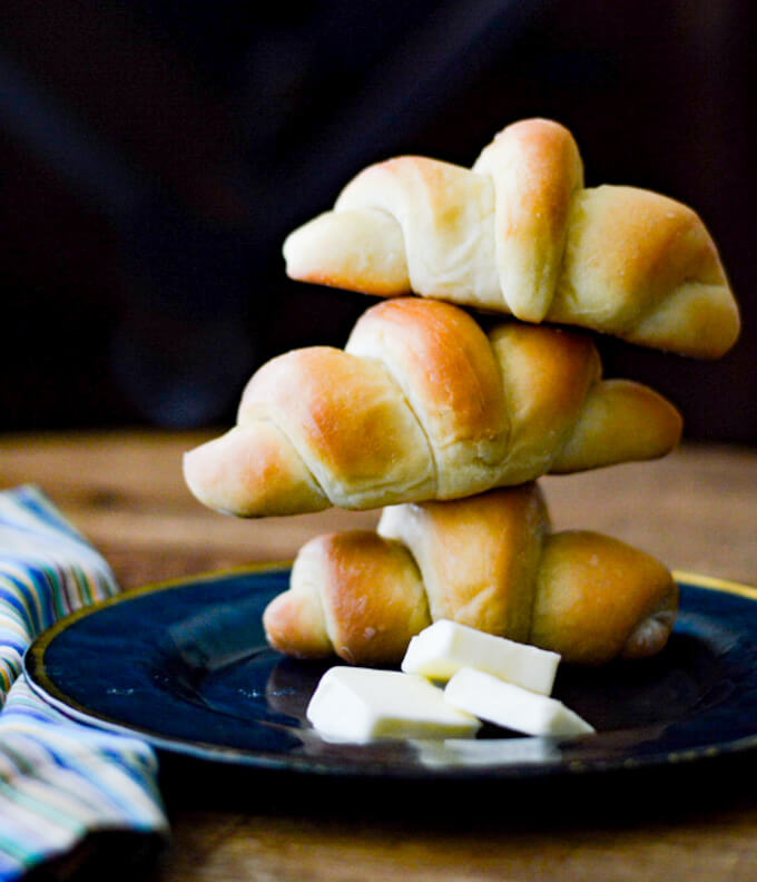 Three crescent yeast rolls stacked on top of each other on a blue plate with a blue striped napkin.