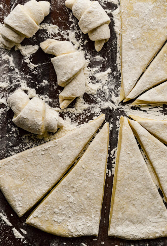 Rolled out bread dough and cut into triangles with 3 crescent shaped rolls.