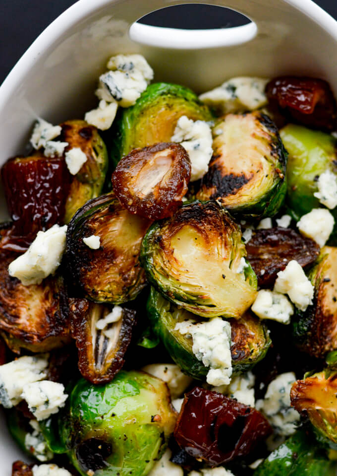Pan roasted brussel sprouts with blue cheese and medjool dates in a white serving bowl.