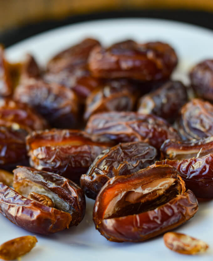 Medjool dates on a white plate.
