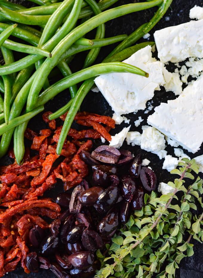 Fresh green beans, kalamata olives, sundried tomatoes, fresh oregano and feta cheese on a black tray.