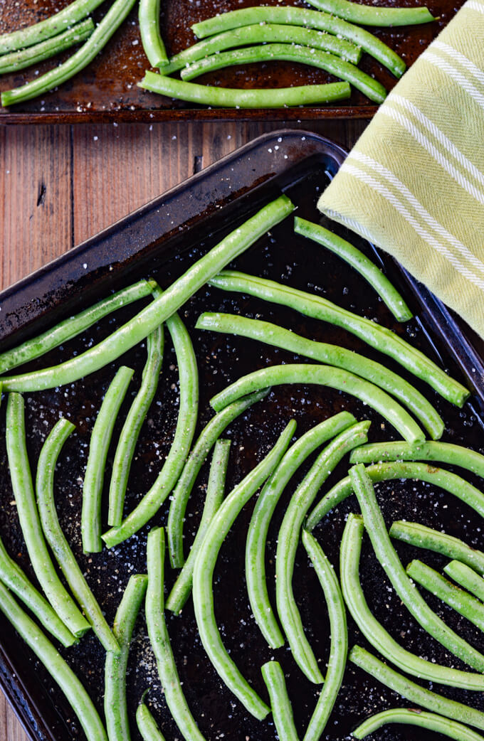 A cookie sheet with fresh green beans with a green dish towel next to it.