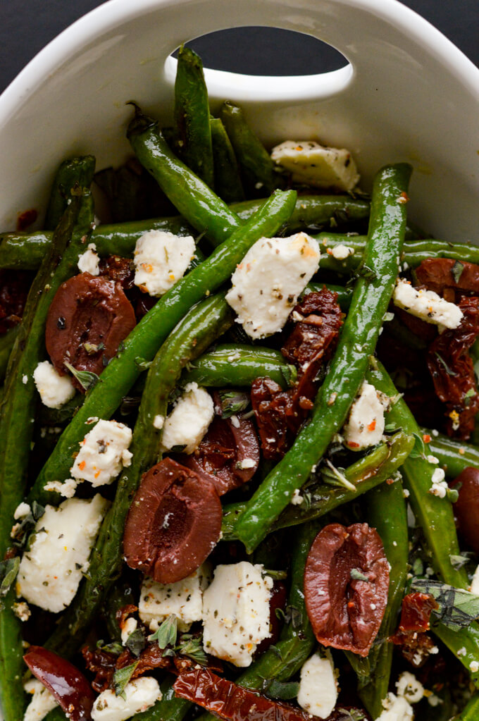 A white bowl of fresh roasted green beans, sundried tomatoes, kalamata olives and feta cheese.