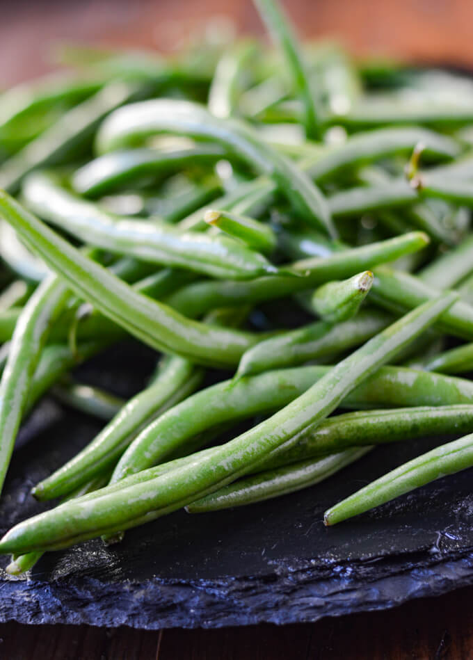 A bunch of fresh green beans on a black tray.