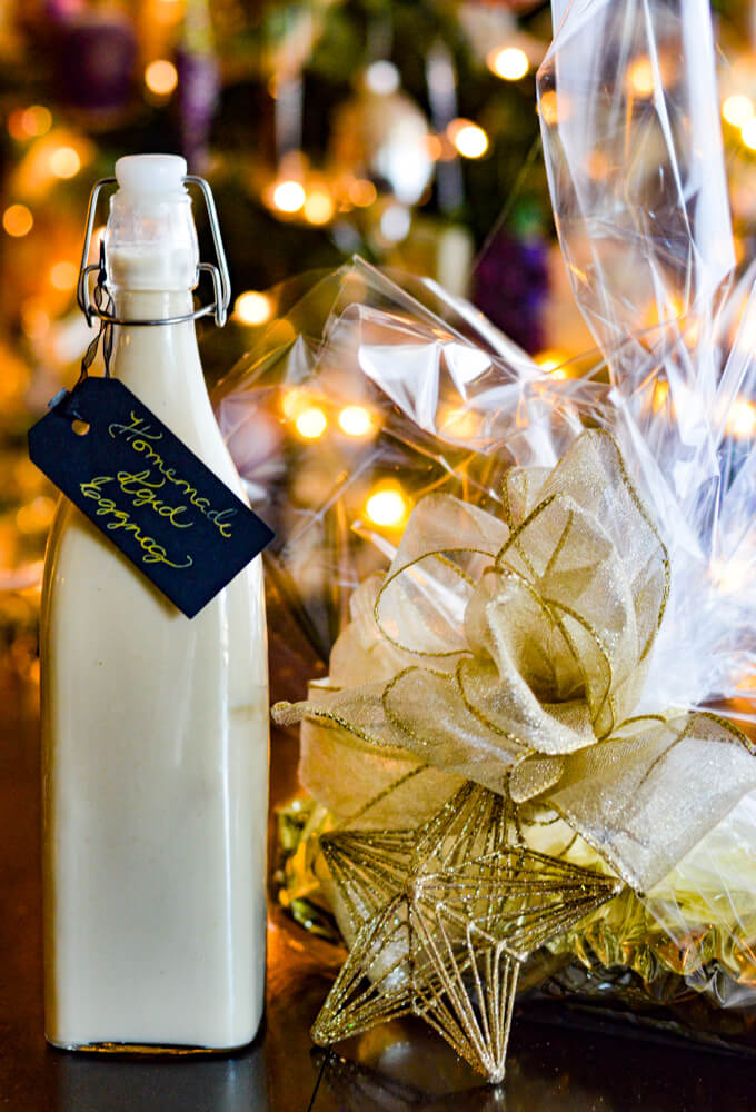 A gift wrapped pumpkin cake roll with cellophane wrap and a white ribbon. A gold star ornament is tied to the gift. A jar of homemade eggnog sits next to it.