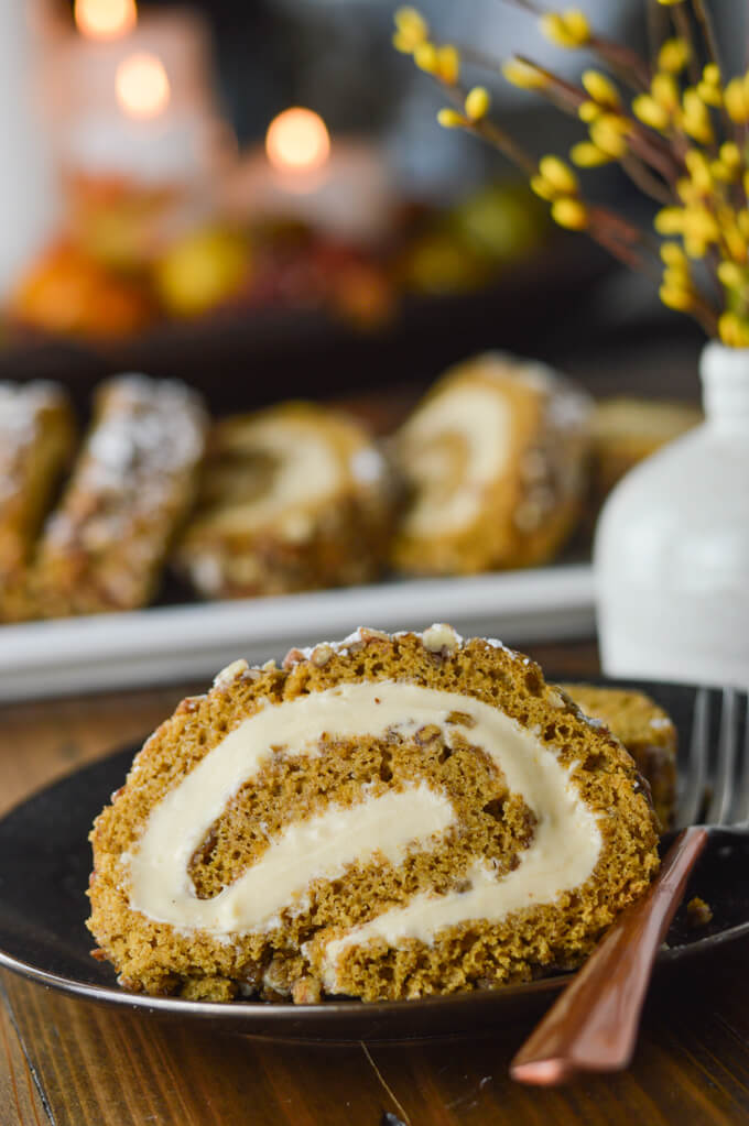 A close-up of a slice of pumpkin cake roll sits on a black plate with a fork. There's a small white vase with yellow sprigs in it. A pumpkin roll with three slices sit in the background and candles lit in a container in the back is blurred out.
