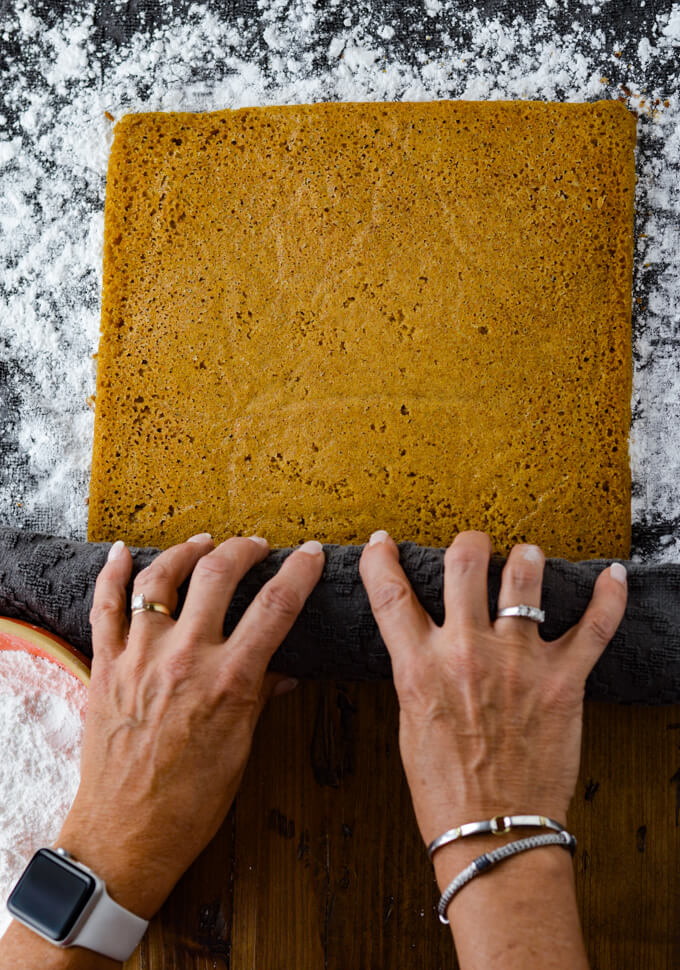 Two hands are rolling up a baked pumpkin cake in a gray powder sugared dish towel. A small orange bowl holding powder sugar sits in the corner.