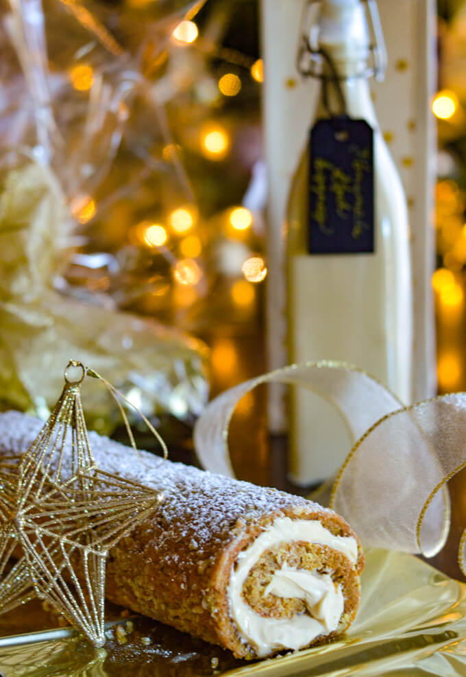 A pumpkin cake roll with homemade eggnog in the background and Christmas decorations around.