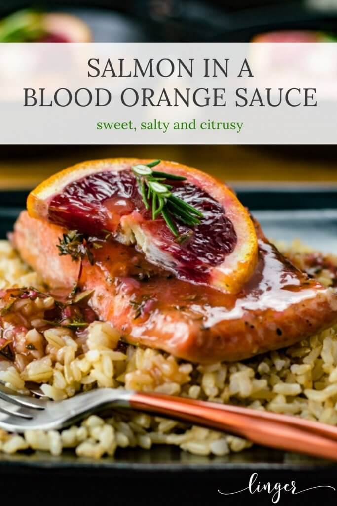 A piece of salmon with blood orange sauce sits atop a bed of rice. A half slice of blood orange with a small sprig of rosemary rests on the salmon. Two salmon pieces are blurred in the background.