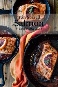 Three cast iron skillets of pan seared salmon in an orange sauce with a colorful orange napkin between them.