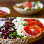A bowl of arugula salad with kalamata olives, feta cheese, red onions and blood oranges. A small bowl of blood orange slices and another salad are in the background.