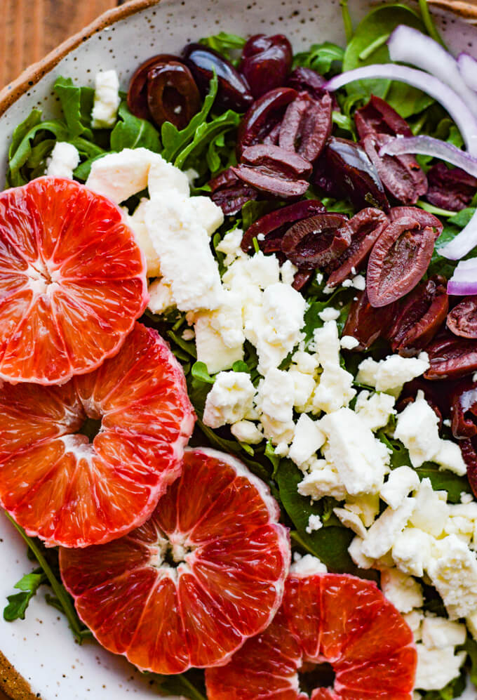 A closeup view of a bowl of arugula salad with kalamata olives, feta cheese, red onions and blood oranges.
