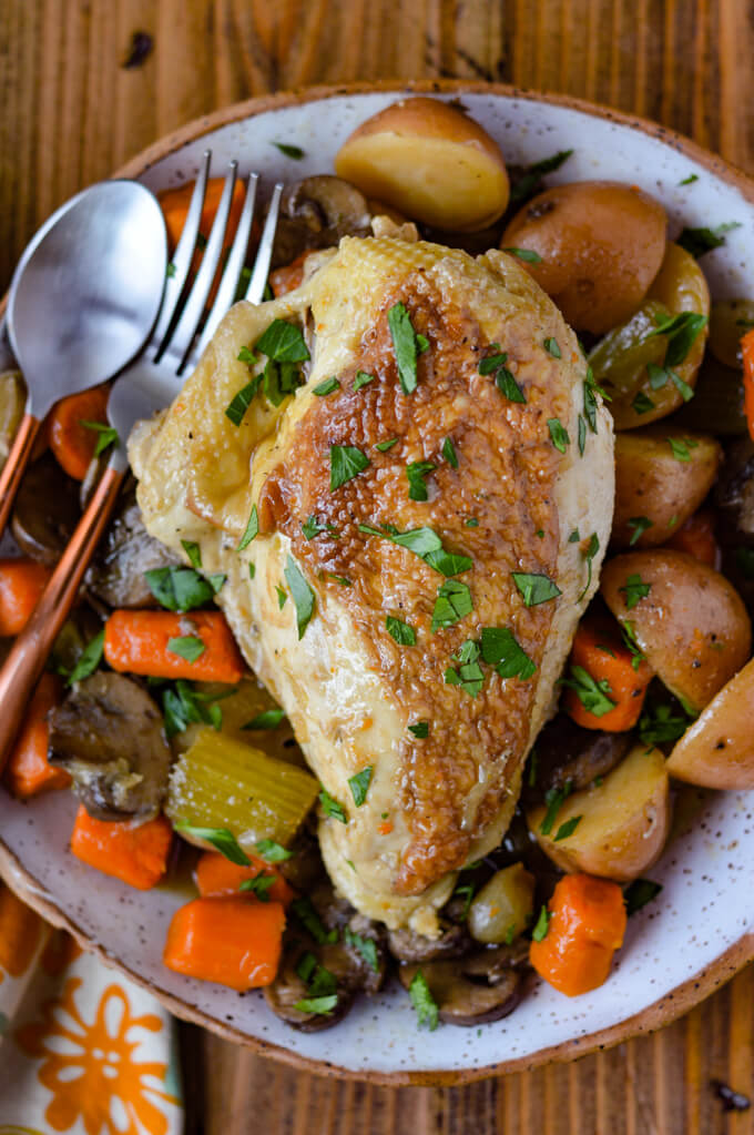 A cooked chicken breast on a bed of cooked carrots, potatoes and celery with a spoon and fork.