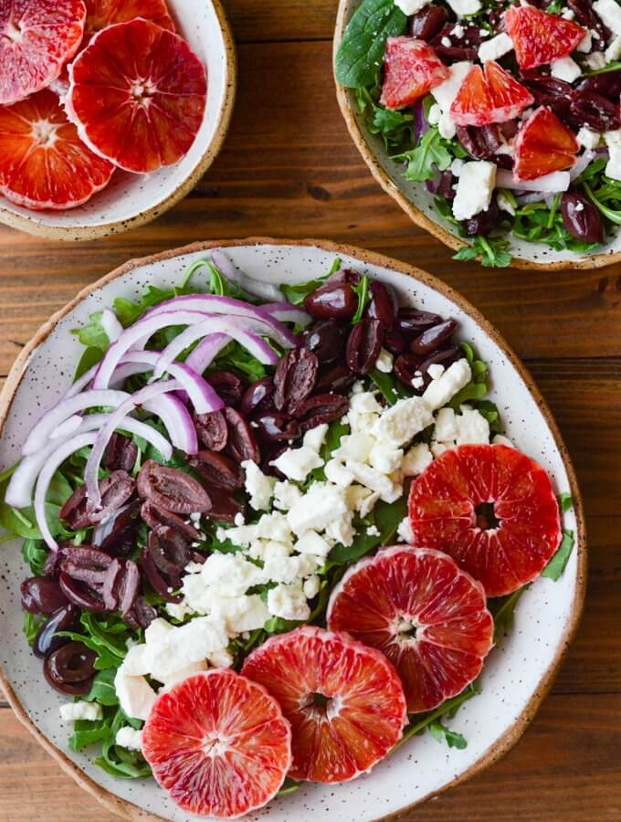 A bowl of arugula salad with kalamata olives, feta cheese, red onions and blood oranges. A small bowl of blood orange slices and another salad are off to the side.