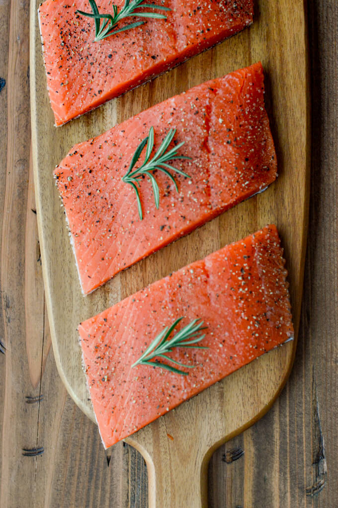 Three uncooked salmon fillets with a small rosemary sprig on each of them. The salmon are on a wooden cutting board.