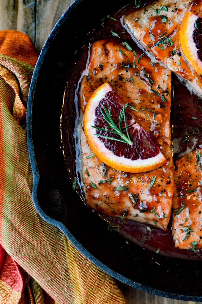Three pan seared salmon in an orange sauce in a cast iron skillet. The salmon have a half orange slice on top and a small rosemary sprig. A orange colored napkin is next to the skillet.
