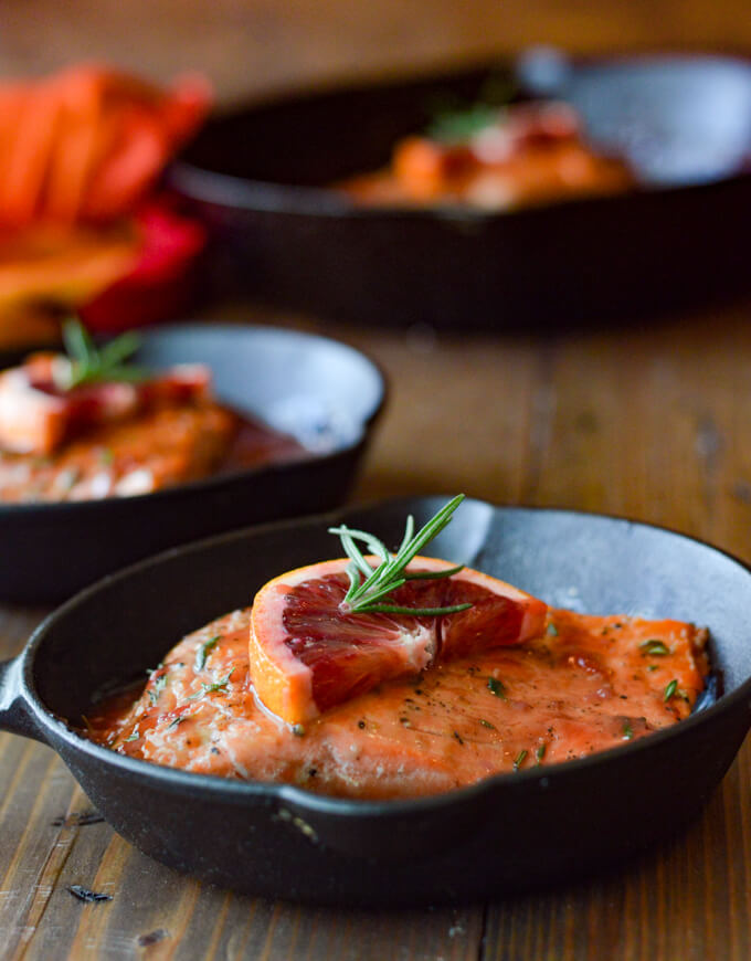 Three small cast iron skillets with one pan seared salmon in an orange sauce.
