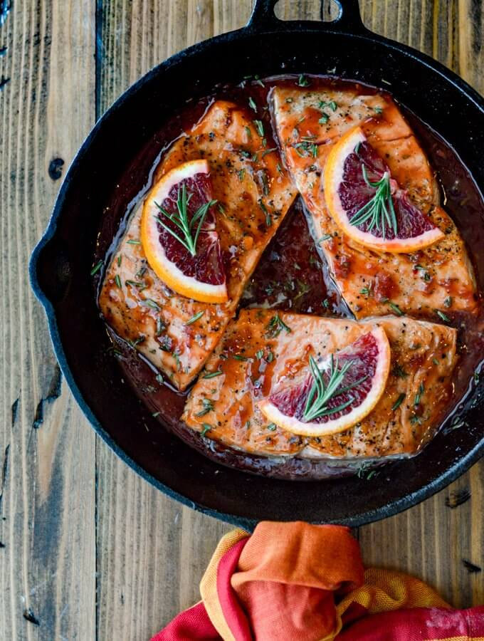 Three pan seared salmon in an orange sauce in a cast iron skillet. The handle has an orange and red napkin around it.