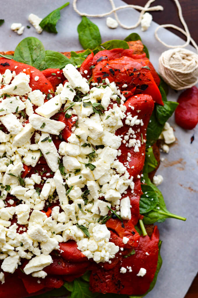 A raw butterflied pork roast with spinach, roasted red peppers and feta cheese on top.