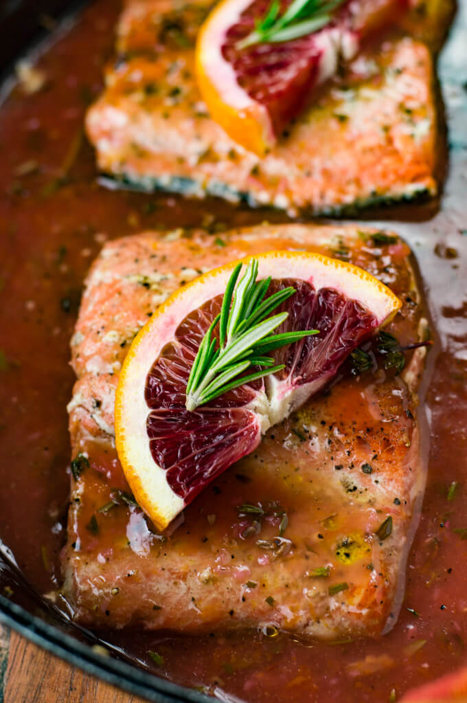 A close-up view of a piece of pan seared salmon in a blood orange sauce. A half slice of blood orange and a small sprig of rosemary sit on top.