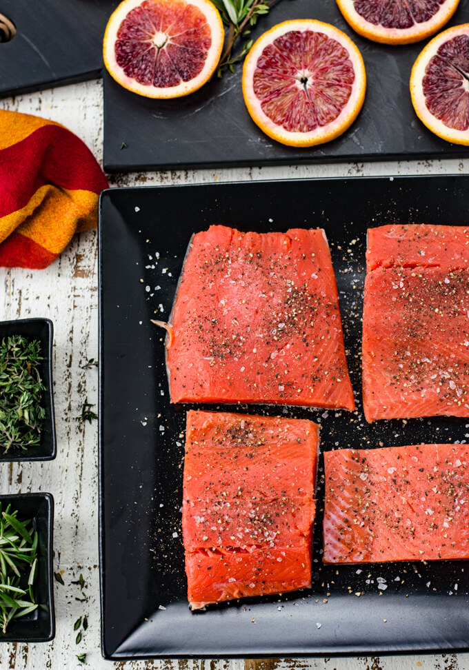 Four pieces of salmon sprinkled with salt and pepper sit on a black plate. Slices of blood oranges sit on a black cutting board above the salmon in the photo. A red and orange napkin and 2 small black bowls with thyme and rosemary sit next to the salmon.