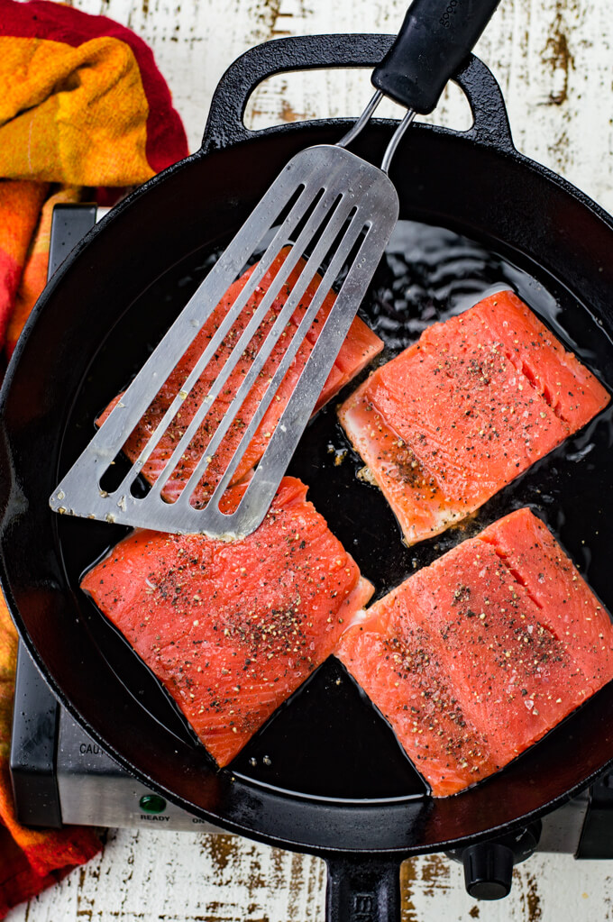 Four pieces of salmon are cooking in a black cast iron skillet. A fish spatula sits on top of them. A red and orange napkin is next to the skillet.